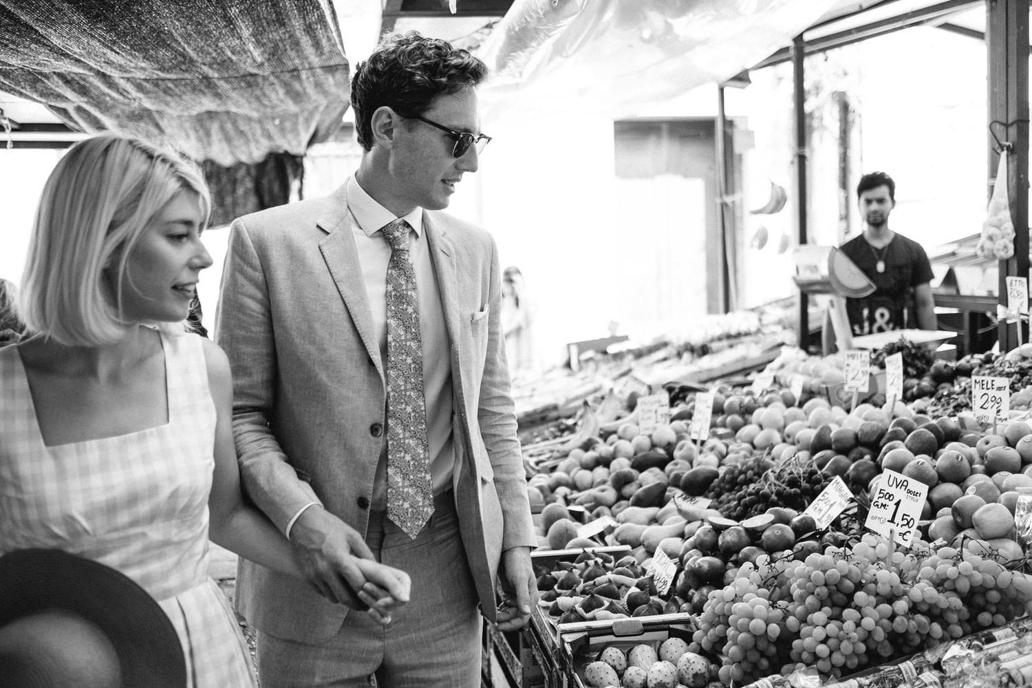 bride and groom walking through the market