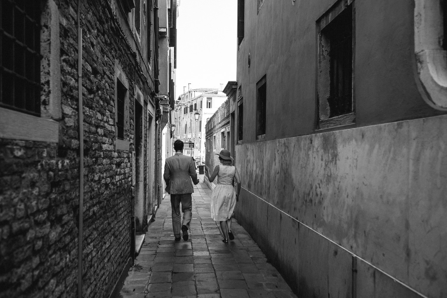 bride and groom walking through the street of venice taken with