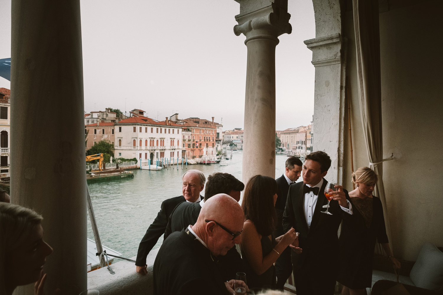 guests enjoy drinks on the balcony in venice by destination wedd