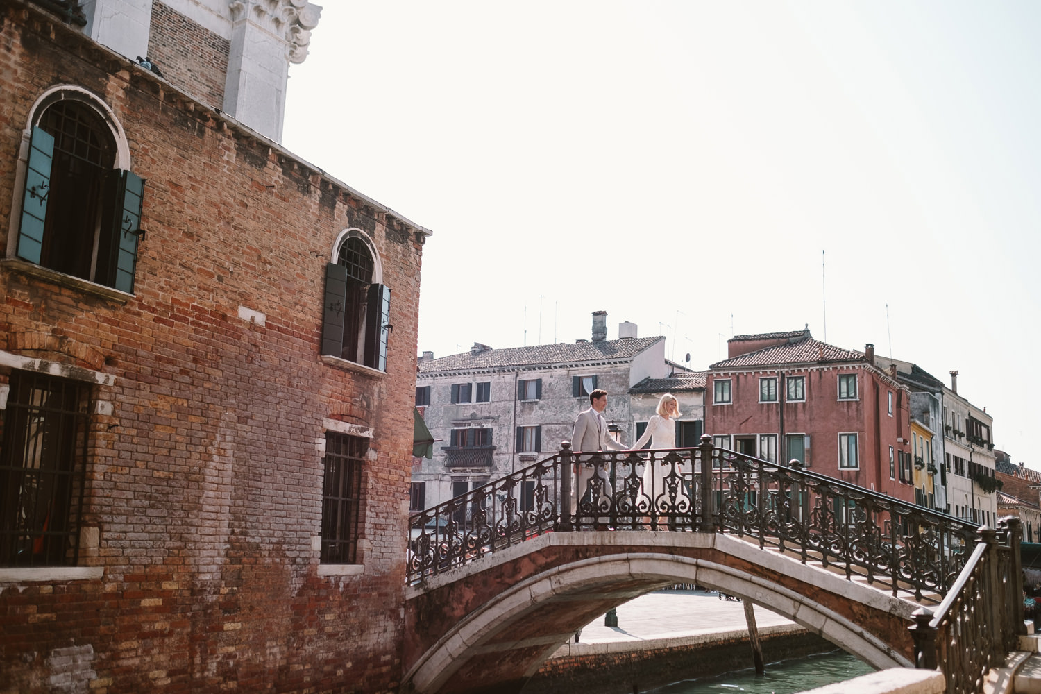 bride and groom walking over a bridge in venice