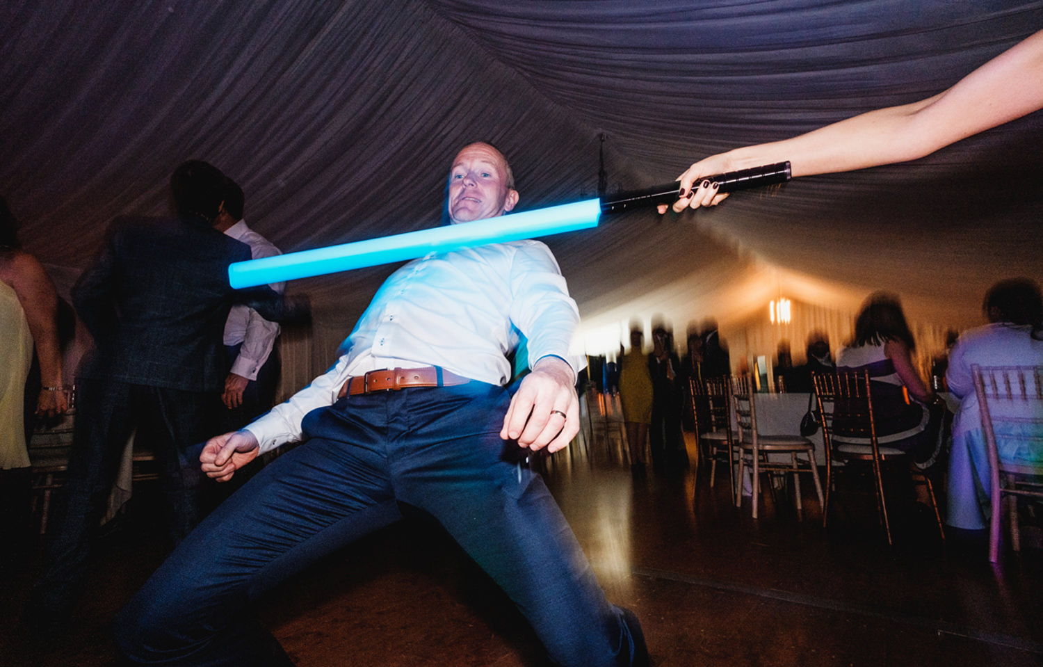 wedding guests dance with a light saber