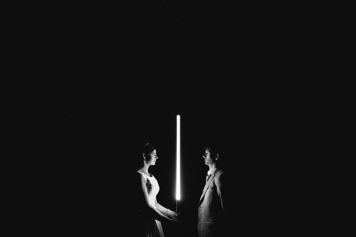 bride and groom pose with light saber in the dark