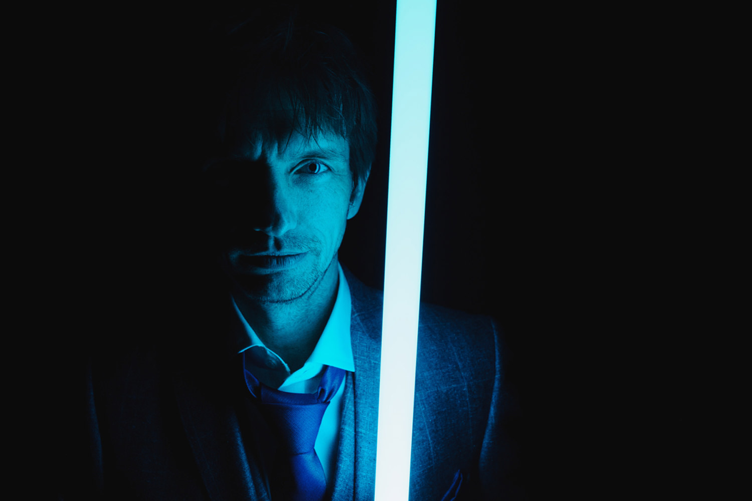 bride and groom pose with light saber from star wars in the dark