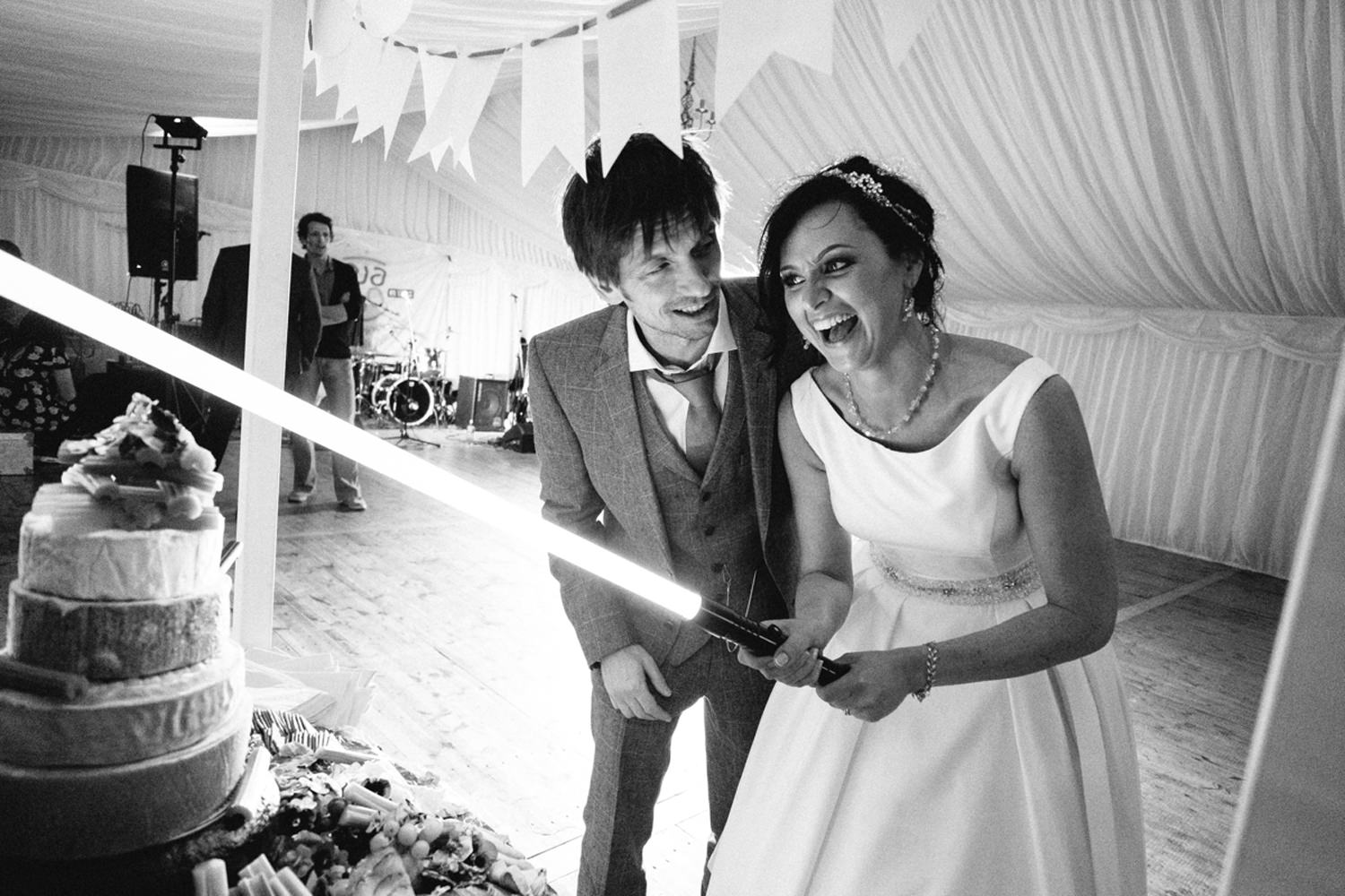 bride and groom cut cake with light saber